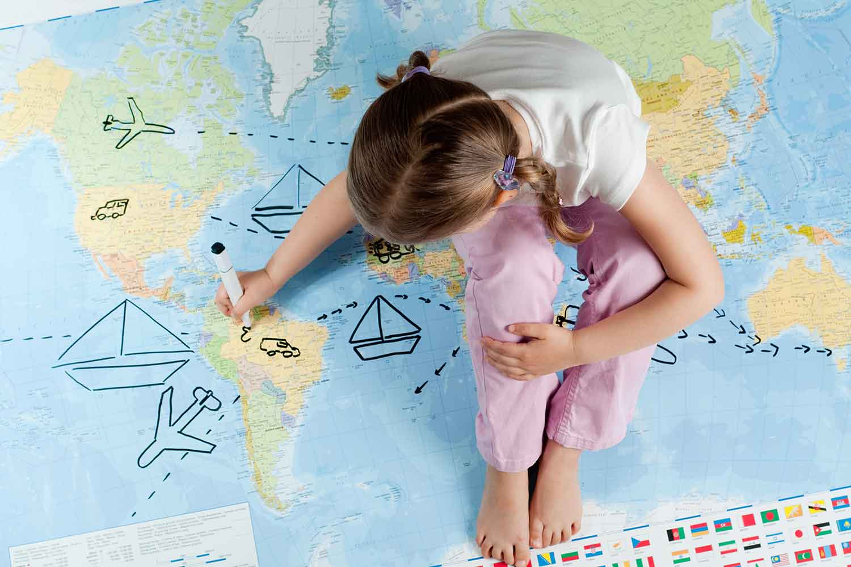 Kind bemalt eine Weltkarte